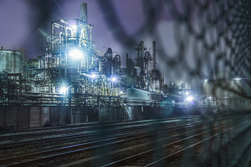 Chemical factories and railroad behind fence at night