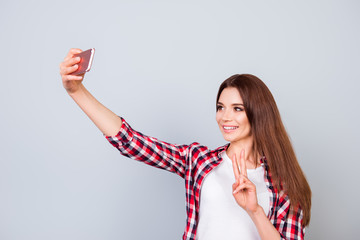 Attractive young brunette cute lady is making a selfie on the camera of her pda, flirty and playful. In casual wear, on pure light background, showing peace sign