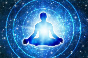 silhouette of a man sitting in a yoga pose of lotus over blue Universe like a concept of meditation and spiritual journey and power of mind