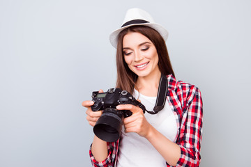 Young attractive brunette photographer is smiling on the blue background. She is excited and holding camera, wearing summer  hat, watching the photos