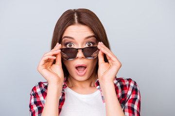Cute amazed brunette girl tourist in shirt, holding her trendy glasses, she is shocked, with wide open eyes and mouth on pure background