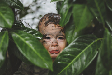 Cute, sad toddler boy crying in the bushes with face covered in mud - funny
