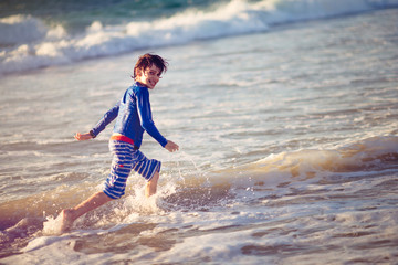 Boy catching waves with a skim board