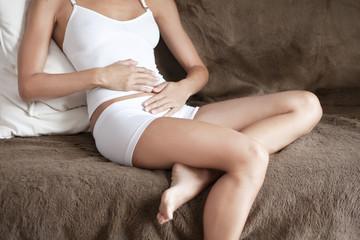 femme qui a mal au ventre sur un canapé