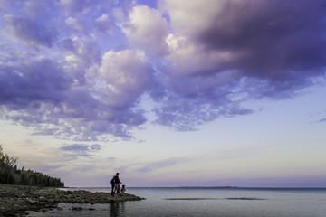 Family Skipping Rocks By Lakeshore At Dusk
