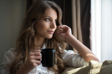 a young brunette relaxing with a cup of coffee