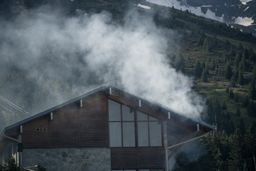 Wooden house with misty mountains landscape in background