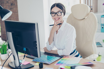 Successful attractive business lady designer is sitting at her work station with stylus, in formal wear, glasses, such a cute smart professional