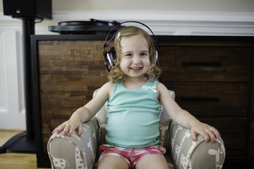 Cute toddler listening to music with big headphones
