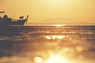 Silhouette of a Thai fisherman wooden boat (longtail) during beautiful sunrise