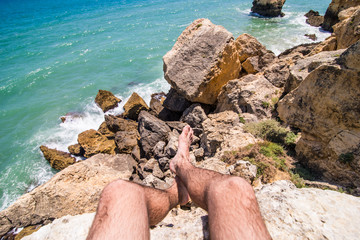 Man legs on caves beach on view on rock