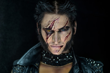 Professional make-up werewolf Wolverine with scars and orange eye