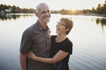 Content middle aged, retired couple laughing together outside on lake ocean dock
