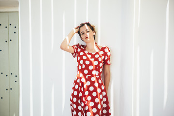 Young woman dressed with red dress with polka dots
