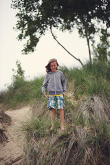 A Boy Is Ready To Jump Off The Edge Of A Sand Dune At The Beach