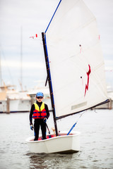 Boy heads out from the yacht club in his dinghy