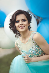 Happy girl in prom with helium air balloons. Portrait of a beautiful girl graduate in a blue dress.
