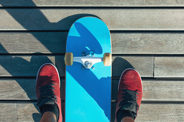 Overhead of blue skateboard on wooden floor.