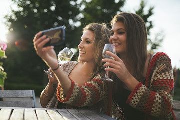 Young women taking a selfie sitting at cafe