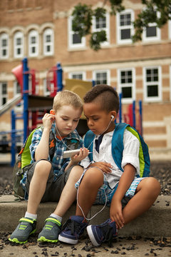 Two boys sharing headset while looking at smartphone
