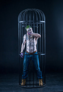 Grim evil character with drawings on the body in the crate. green hair