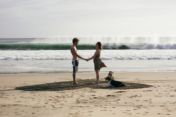 Love couple standing in a heart shape on the beach