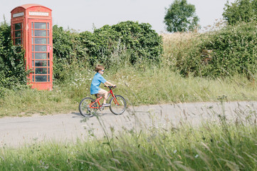 Boy riding bicycle in English countryside