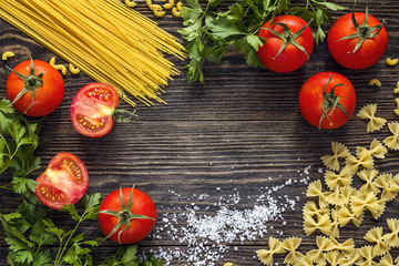 Background with pasta, tomatoes and herb on dark wooden table with copy space.