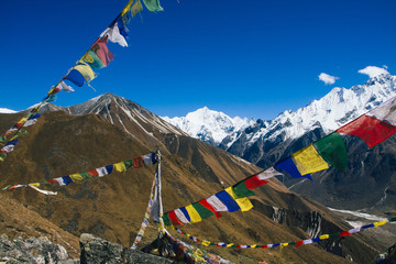 Prayer flags fluttering in the wind high up in the himalayan mountains