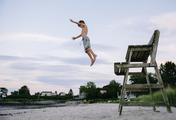 Boy jumps off lifeguard tower while playing on a beach in the evening