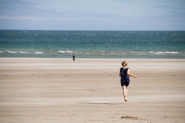 Children running away on a beach