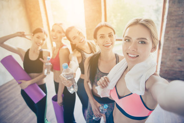 Selfie mania in gym! Five girlfriends in fashionable sport outfits are posing for a selfie photo, that blond is taking. They are all smiling, joyful after the workout