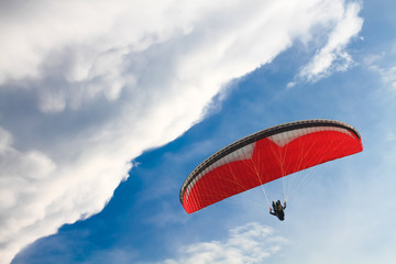 Red Paraglider against the Blue Sky with Clouds