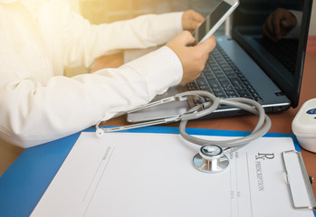 Stethoscope on prescription clipboard and Doctor working an Laptop computer and smart phone on desk in hospital, Healthcare and medical concept, selective focus