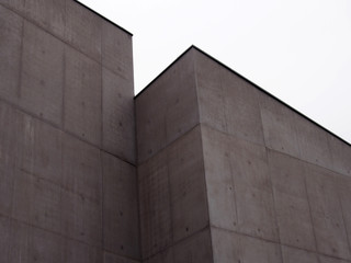 angular stark concrete walls with corners and white sky with rectangualr panels and regular marks