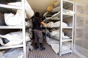 Member of Libyan anti-crime service points to dead bodies of Islamic State militants, at a morgue in Misrata