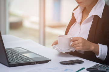 A business woman working and holding coffee cup at the office desk.