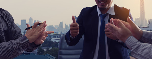 A group of happy businesspeople clapping hands and thumbs up expresses happiness and success.