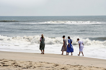 Amish or Mennonite women walking along Atlantic beach shoreline.