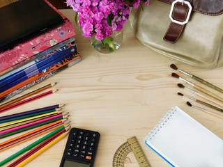 School supplies on a wooden table. Empty place for a text in the middle