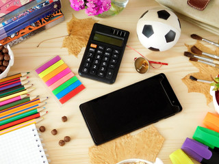 Smartphone with an empty screen and calculator surrounded by school supplies on a wooden background