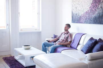 Adult man sitting on a sofa and changing television channel with a remote control