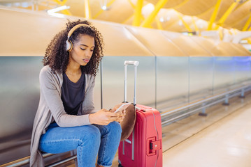 happy young woman listening music with headphones and mobile phone at the airport