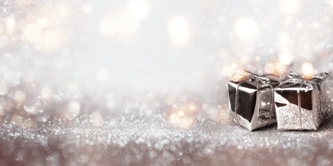 Shiny gifts on a silver bokeh background