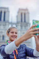 Teenager tourist girl is taking selfie with cathedral of Notre Dame de Paris. France.