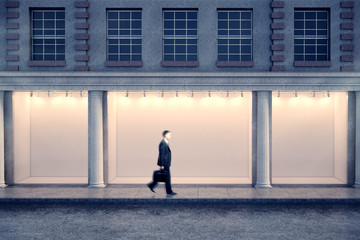 Man passing storefront at night