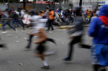 Demonstrators run away while clashing with riot security forces during a rally against Venezuela's President Nicolas Maduro's government in Caracas