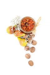 Pear jam with walnuts in a glass jar on a white background top view..