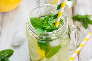 Homemade lemonade. Water with lemon, mint  and ice in glass on a white wooden background. Rustic style.