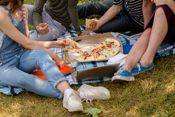 Pizza time for students in campus. Young people having lunch on grass.